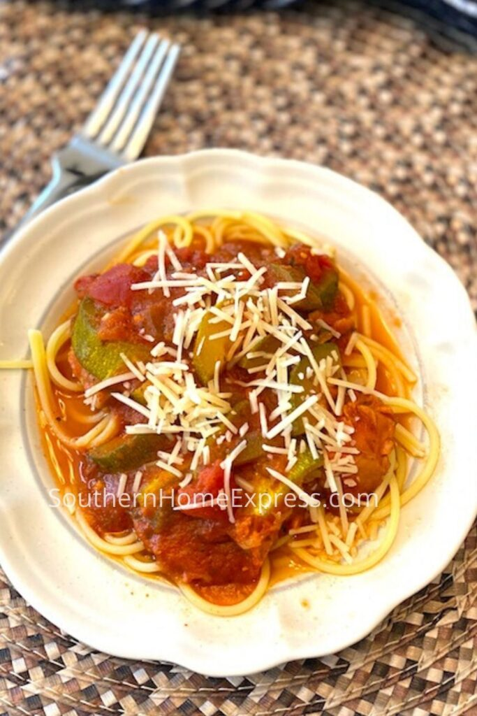 Serving of spaghetti with zucchini pasta sauce and shredded Parmesan cheese