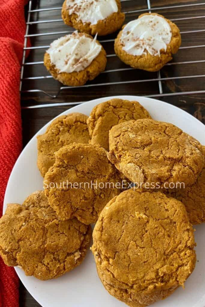Platter of pumpkin cookies beside a cooling rack with more cookies