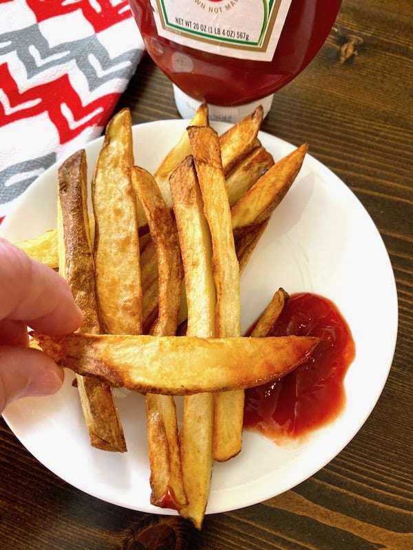Dipping a french fry in some ketchup