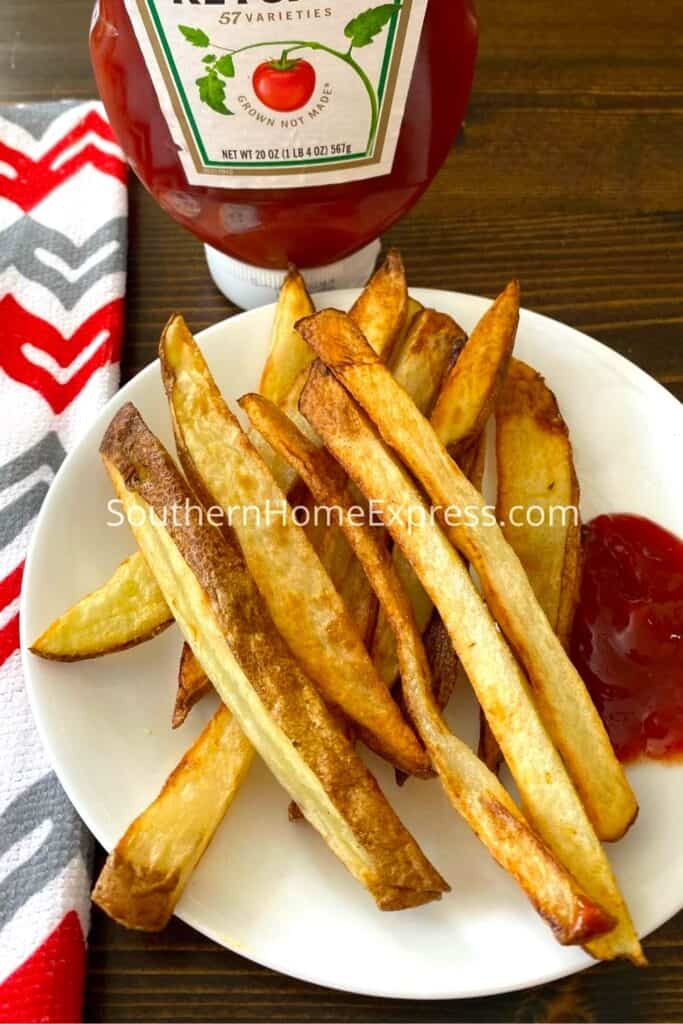 Plate of french fries on a plate with ketchup