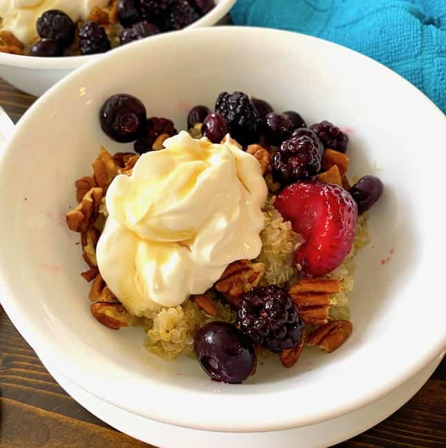 Bowl filled with quinoa, berries, nuts, and yogurt