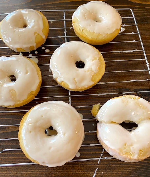 Frosted donuts on a baking rack