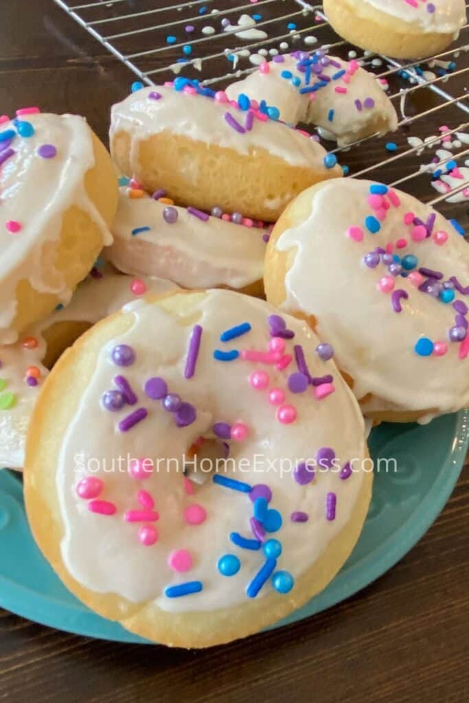 Stack of frosted donuts on a plate with sprinkles all over the tops
