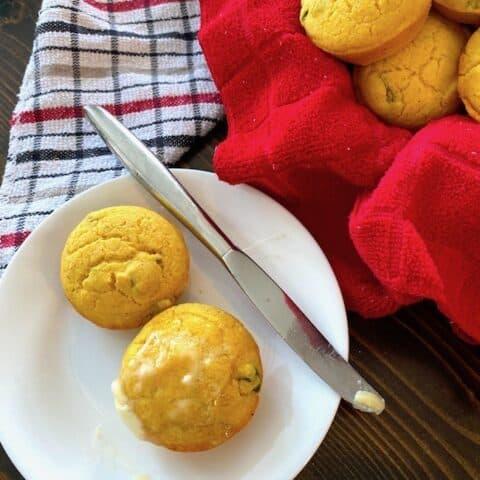 2 jalapeno corn muffins beside a basket of muffins