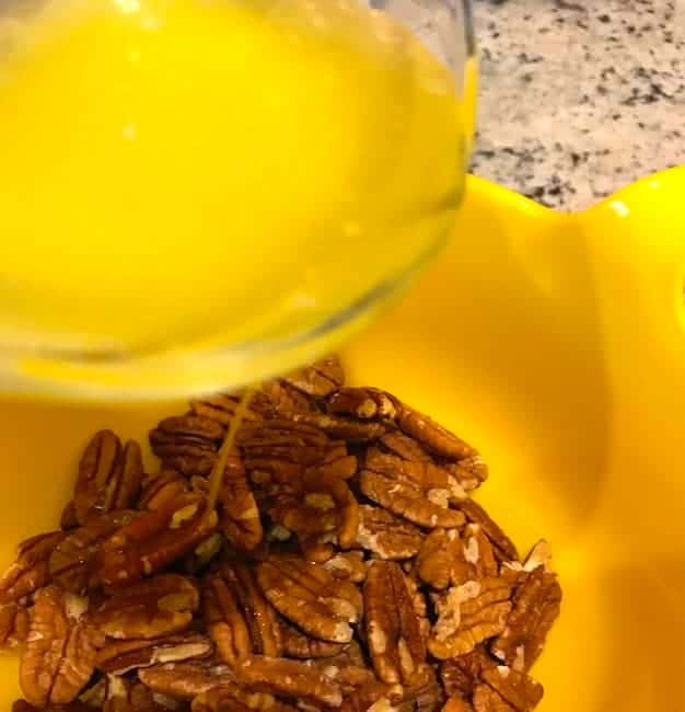 Pouring melted butter over pecans
