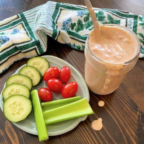Thousand Island dressing next to a plate of vegetables