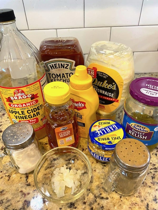 Ketchup, mayonnaise, sweet pickle relish, apple cider vinegar, honey, mustard, minced garlic, chopped onions, salt, and pepper