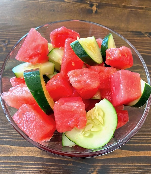 Watermelon cucumber salad in a clear glass serving bowl