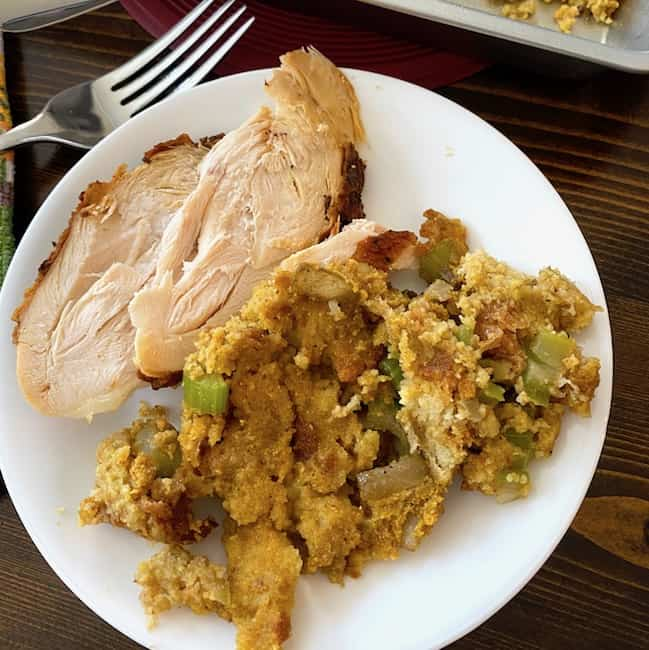 Cornbread dressing on a plate with chicken