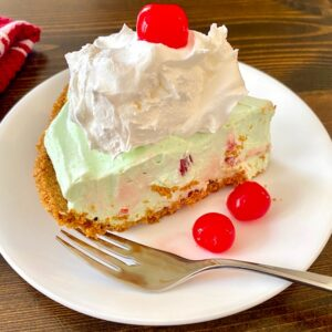 Slice of cherry lime pie with whipped cream and a cherry