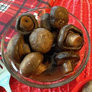 Bowl of marinated mushrooms on a red towel