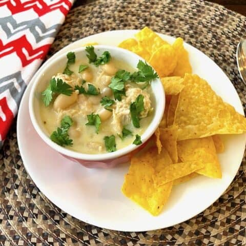 White chicken chili garnished with cilantro in a bowl on a plate with tortilla chips