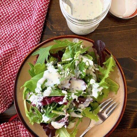 Buttermilk ranch dressing on a salad beside a jar of dressing
