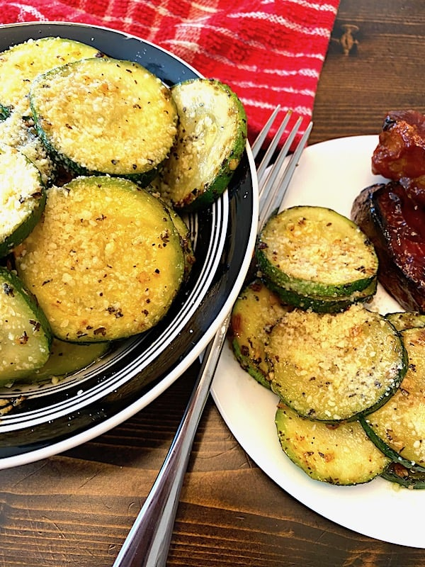 Bowl and plate with garlic zucchini Parmesan