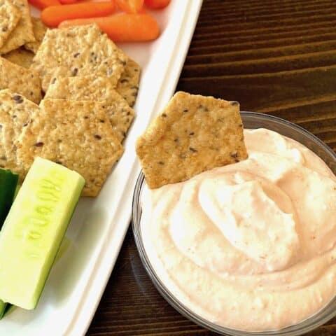 Bowl of dipping sauce beside a plate of vegetables and crackers