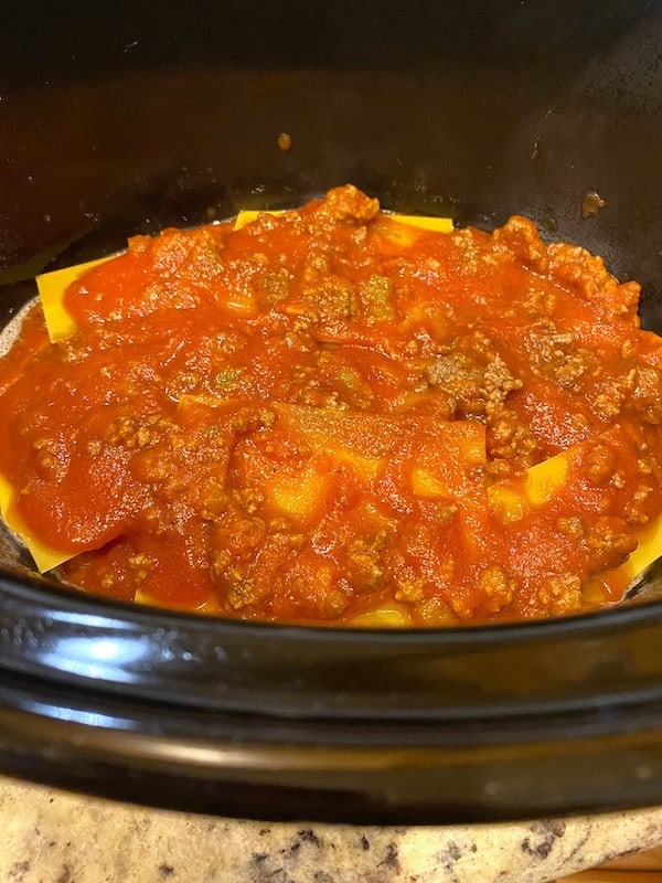 Layers of lasagna and spaghetti meat sauce in a Crock Pot