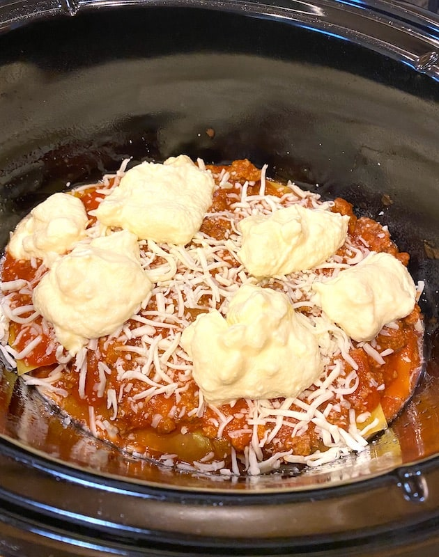 Dollops of ricotta mixture over layers of lasagna, spaghetti meat sauce, and shredded mozzarella in a Crock Pot