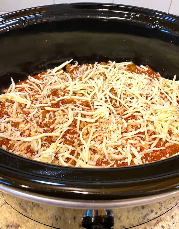 Layers of lasagna ingredients topped with final layer of shredded mozzarella in a Crock Pot
