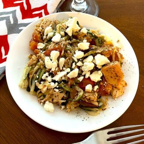 Greek chicken with zoodles and feta on a plate