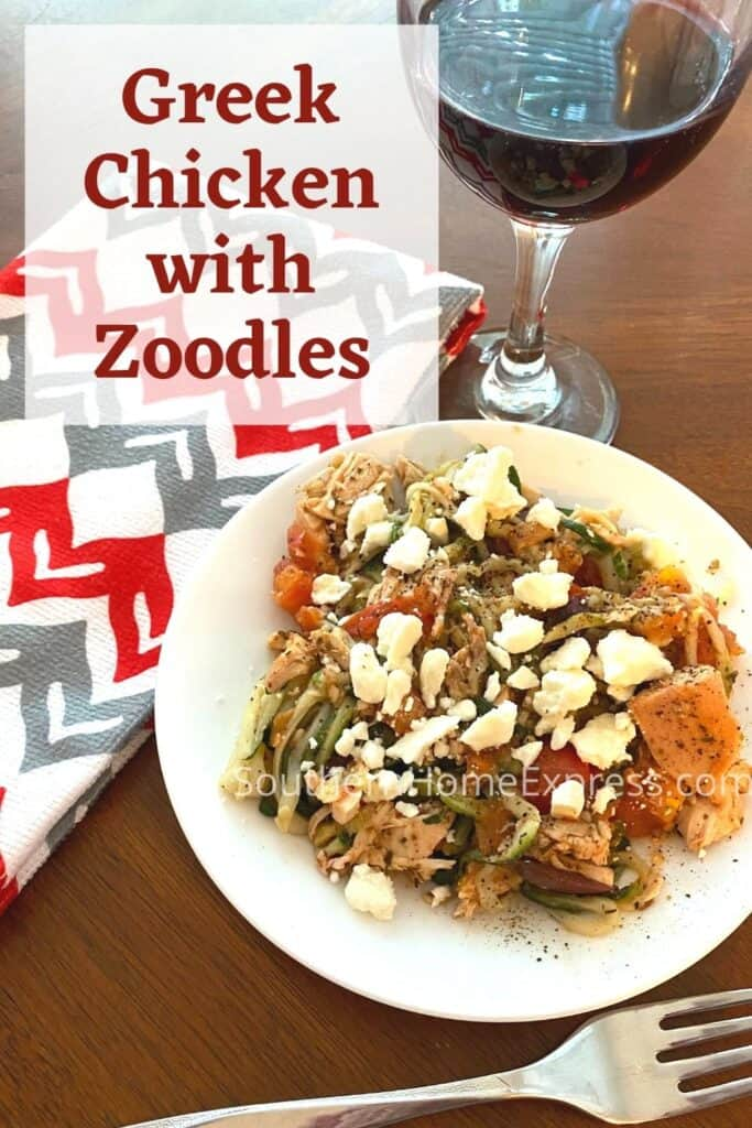 Plate of chicken with zoodles and feta beside a glass of wine