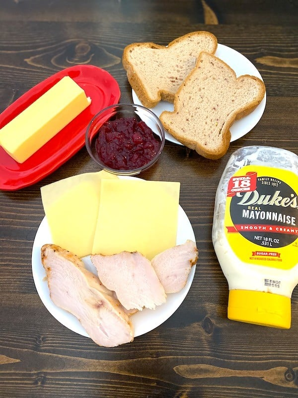 bread, butter, cranberry sauce, turkey, cheese, and mayonnaise