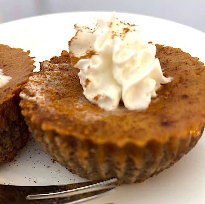 mini pumpkin pie with whipped cream on top and sprinkled with cinnamon