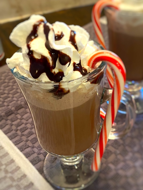 2 mugs of hot cocoa with whipped cream, chocolate syrup, and a candy cane