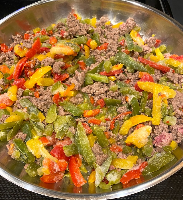 browned ground beef, peppers, and onions in a skillet