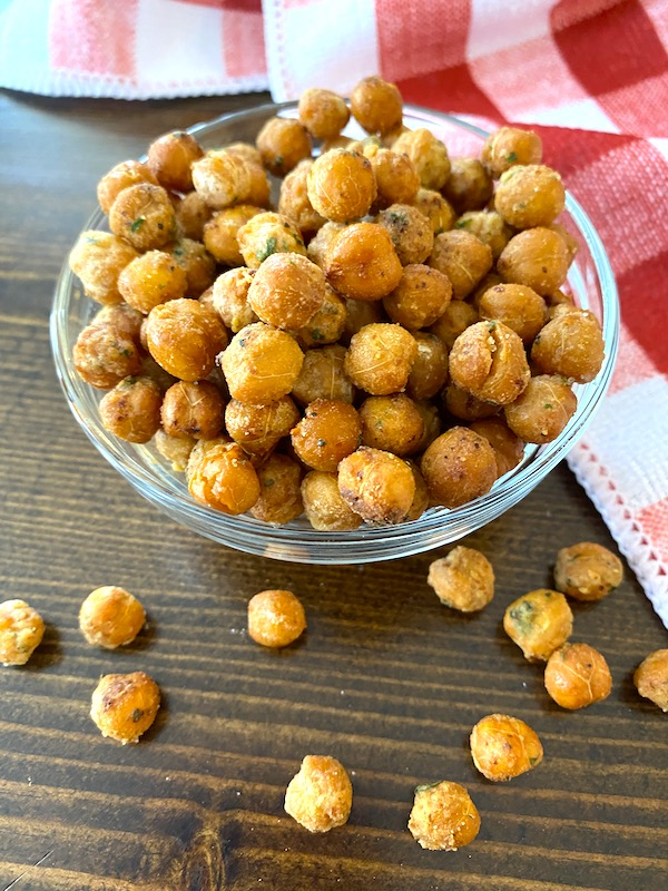 bowl of crispy chickpeas with some scattered on the table beside a red and white towel