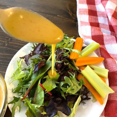 drizzling honey mustard dressing over salad