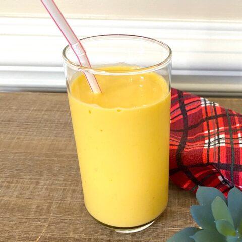 mango smoothie beside a red plaid dishtowel