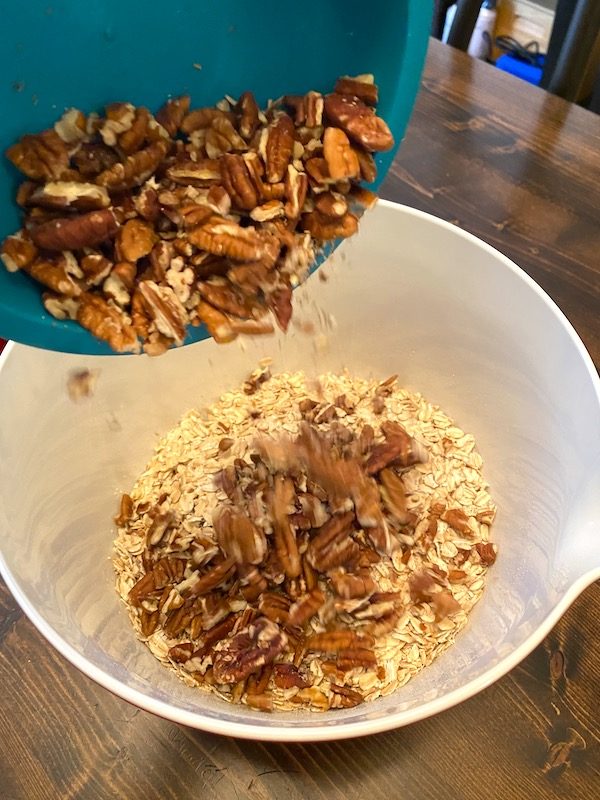 pouring pecans into bowl of oats