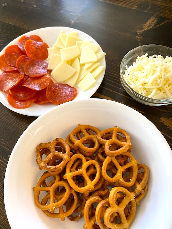 twisted pretzels, slices of pepperoni, sliced cheese, and shredded cheese