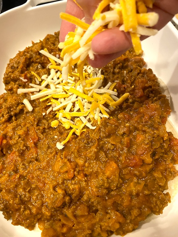 sprinkling cheese over beef and bean mixture