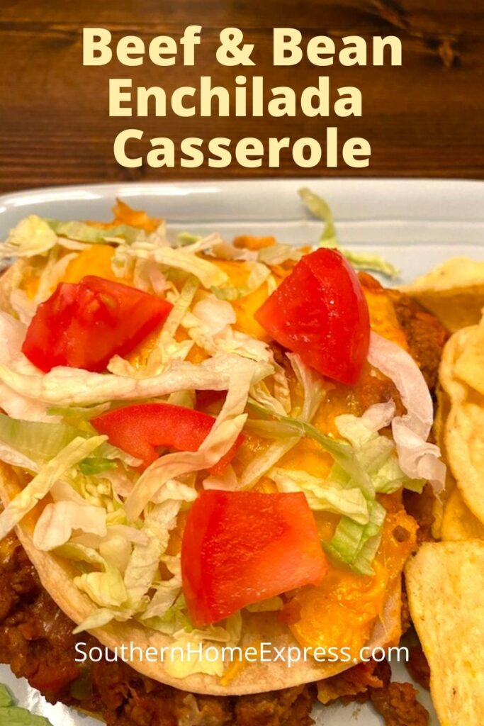 serving of beef and bean enchilada casserole with shredded lettuce and chopped tomatoes on top