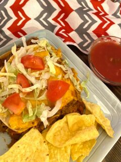 serving of beef and bean enchilada with a side of chips