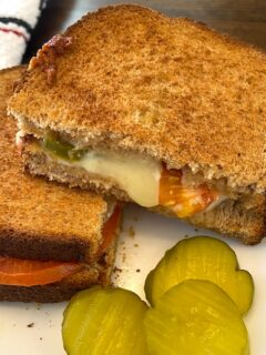 grilled cheese sandwich on a plate with pickle slices