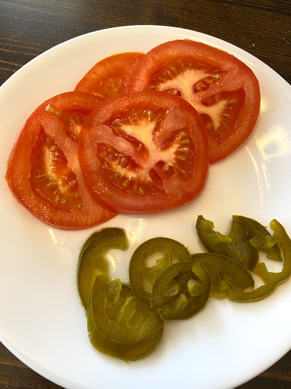 plate of sliced tomatoes and jalapeno peppers