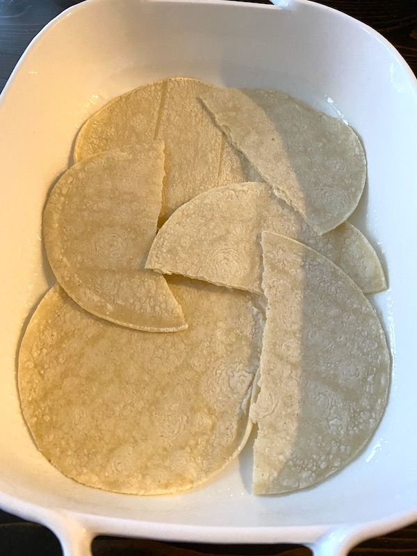 first layer of tortillas lining casserole dish