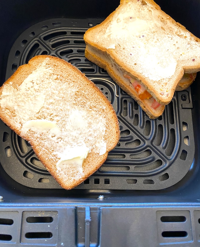 Uncooked cheese sandwiches in air fryer basket.