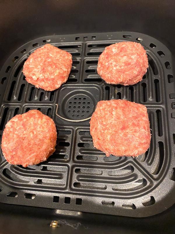 Uncooked sausage patties in an air fryer basket