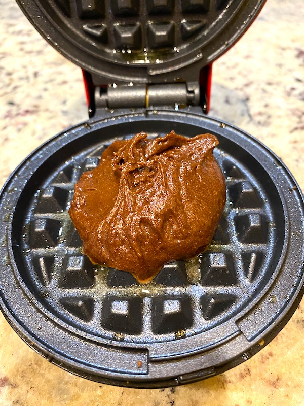scoop of batter in the middle of a waffle iron.