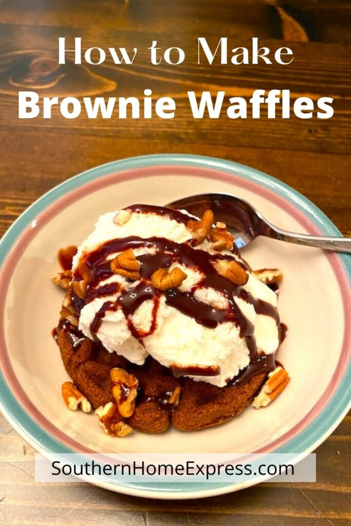 bowl of brownie waffle topped with ice cream, chocolate syrup, and nuts