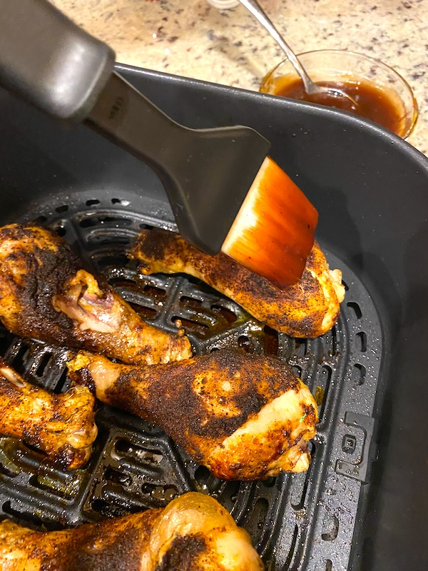 brushing barbecue sauce over dry-rubbed, cooked chicken