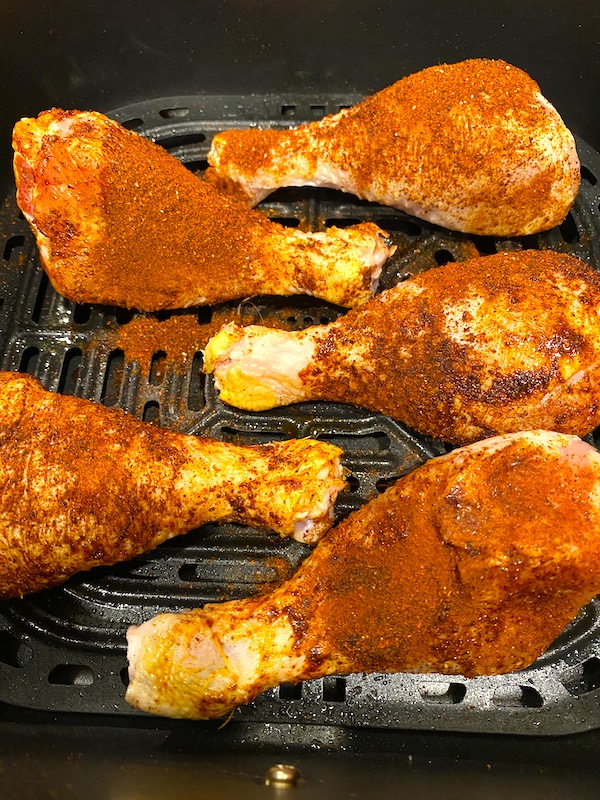 dry-rubbed chicken in an air fryer basket