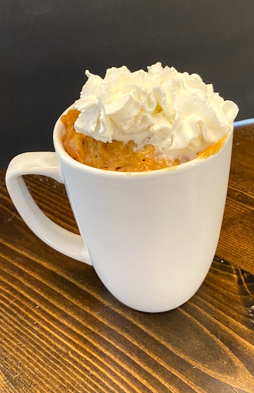 peanut butter cake in a mug with whipped cream.