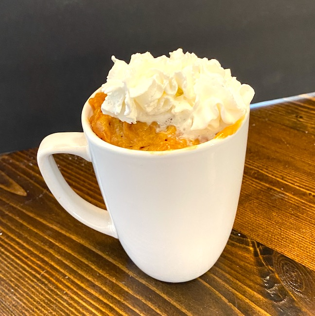 peanut butter cake in a mug with whipped cream on top