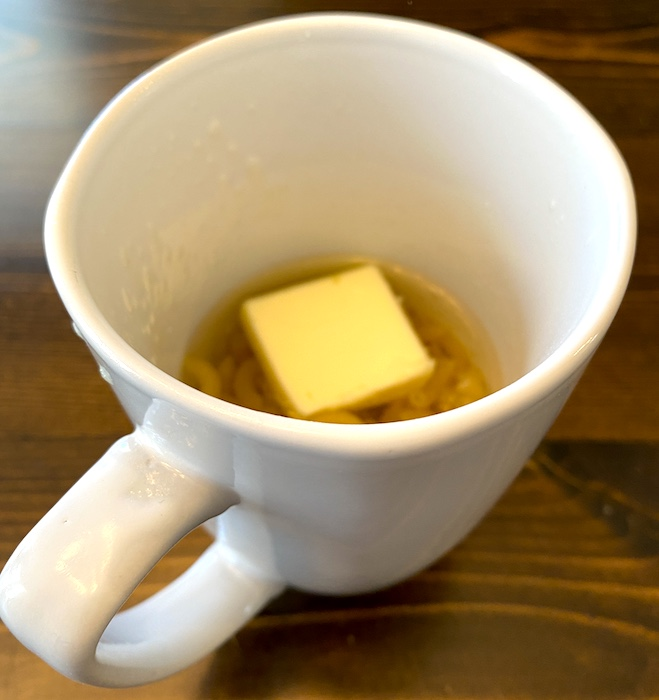 pasta, water, and butter in a mug