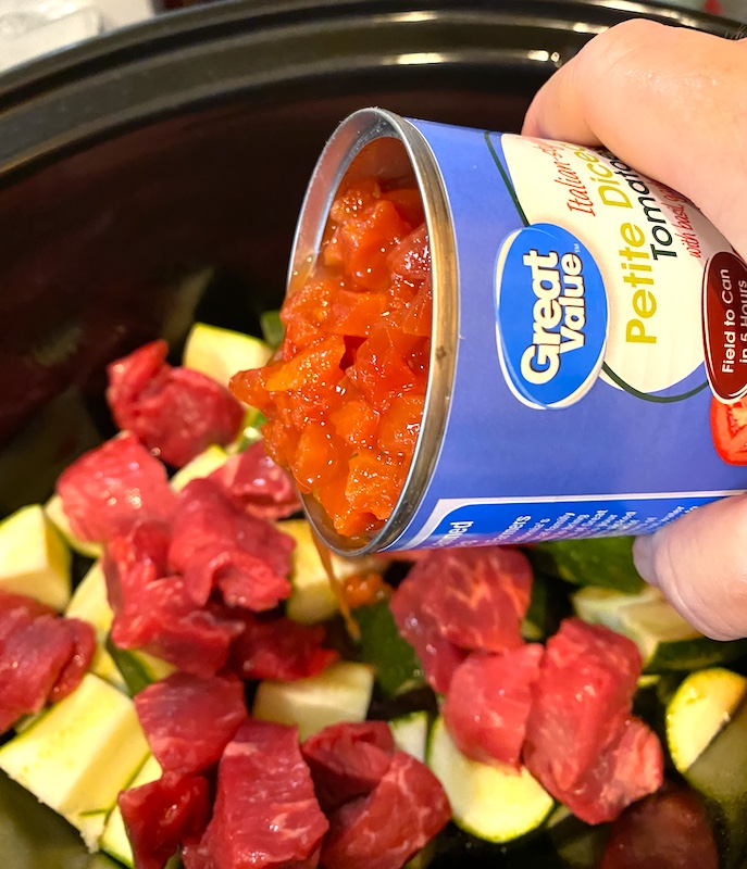 pouring diced tomatoes into the pot with the zucchini and stew meat.