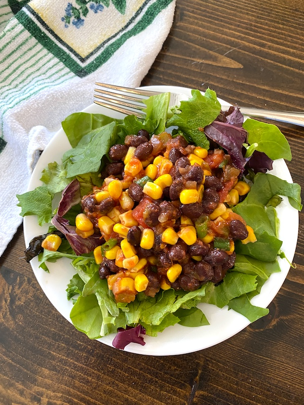 tex mex salad with mixed greens on a plate with a fork and dishtowel